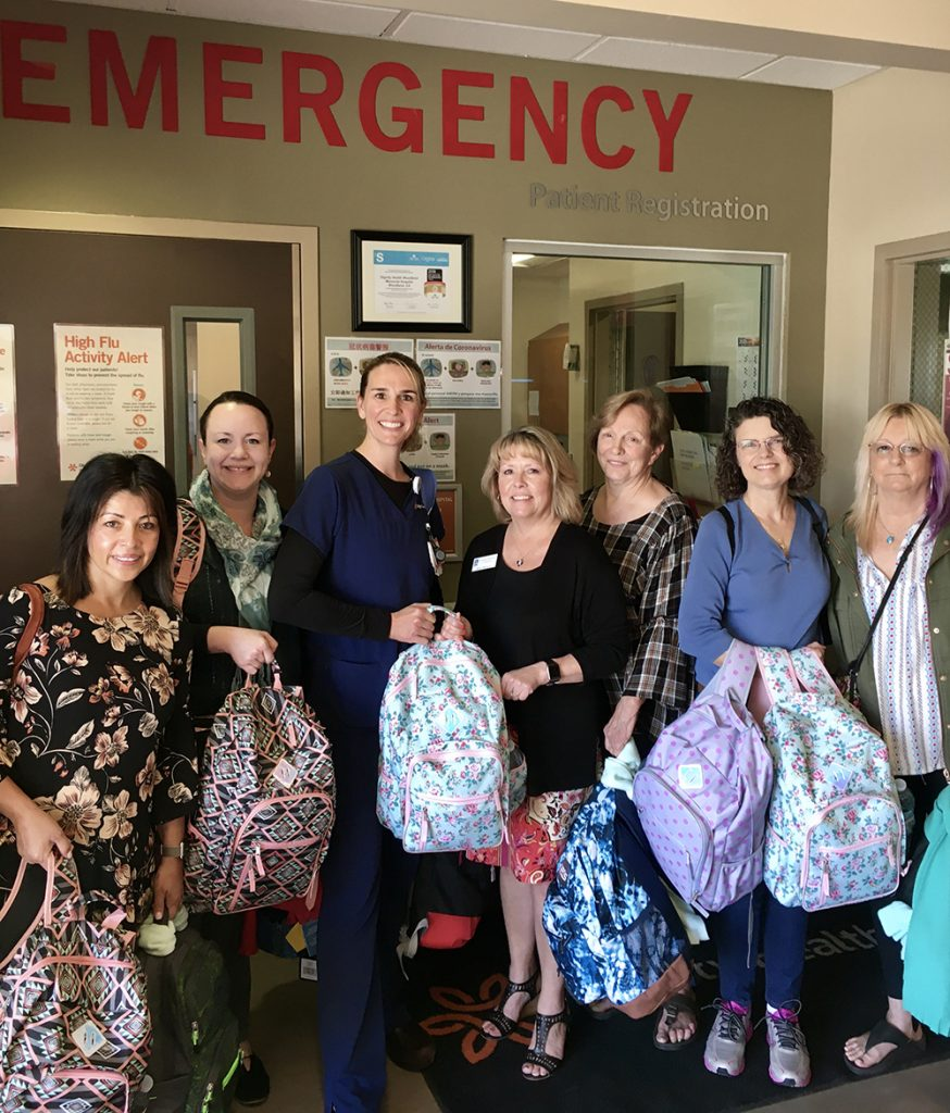 Soroptimists holding assembled backpacks for survivors of human trafficking and domestic violence, given at Empower Yolo and Sutter Health emergency rooms.