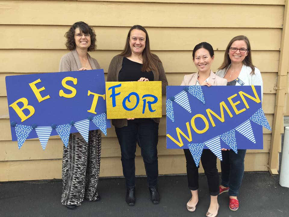 """Members holding up signs that read """"Best for Women"""""""
